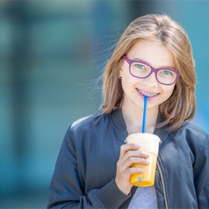 preteen girl with braces smiling and holding a drink